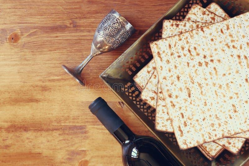 Ideia superior do fundo do passover vinho e matzoh (pão judaico do passover) sobre o fundo de madeira fotografia de stock