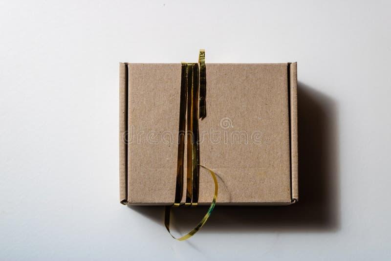 Ideia superior do giftbox fechado do cartão com a fita dourada no fundo branco - imagem fotografia de stock royalty free