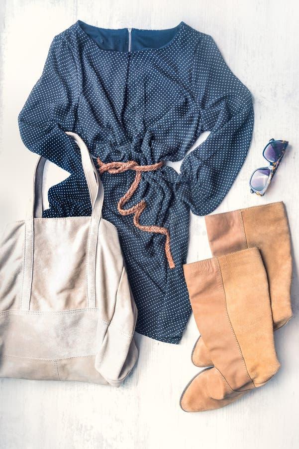 Ideia superior do grupo da roupa da mulher O preto pontilhou o vestido, as botas de couro do marrom e os acessórios sobre o fundo imagem de stock