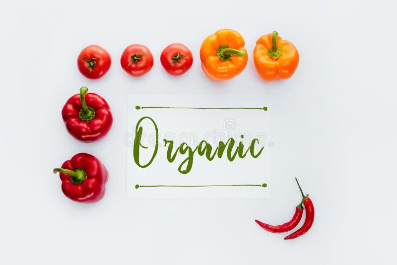 ideia superior do quadro de vegetais vermelhos e alaranjados com a palavra orgânica imagens de stock