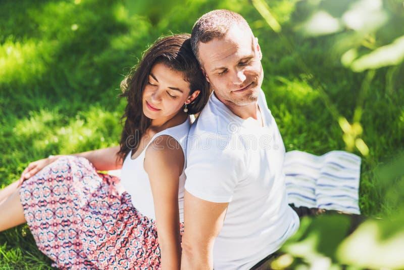 Ideia superior horizontal bonita de um par atrativo no amor que senta-se em uma cobertura do piquenique Homem e morena sonhadores imagens de stock royalty free