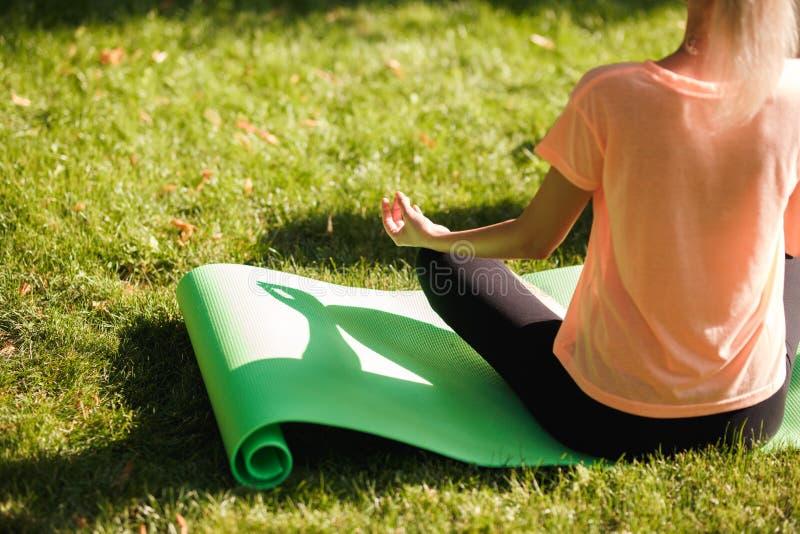 A ideia traseira da ioga praticando da mulher senta-se na posição de lótus Conceito saudável do estilo de vida fotografia de stock