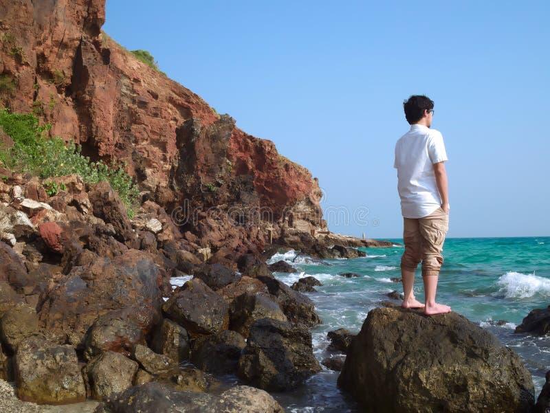 Ideia traseira da posição asiática nova do viajante na rocha da costa de mar imagens de stock royalty free