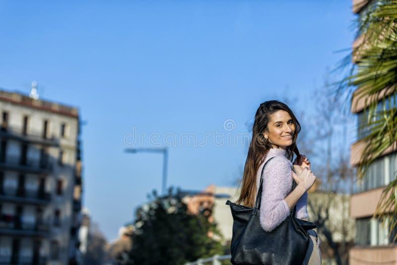 Ideia traseira da posição bonita de sorriso da jovem mulher na rua ao olhar a câmera em um dia ensolarado imagens de stock