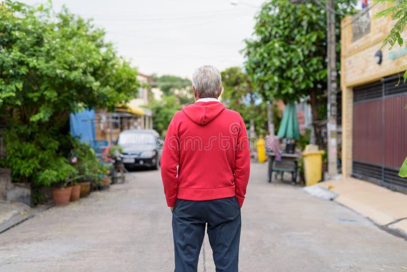 Ideia traseira da posição do homem superior ao vestir o outdoo vermelho do revestimento fotografia de stock royalty free