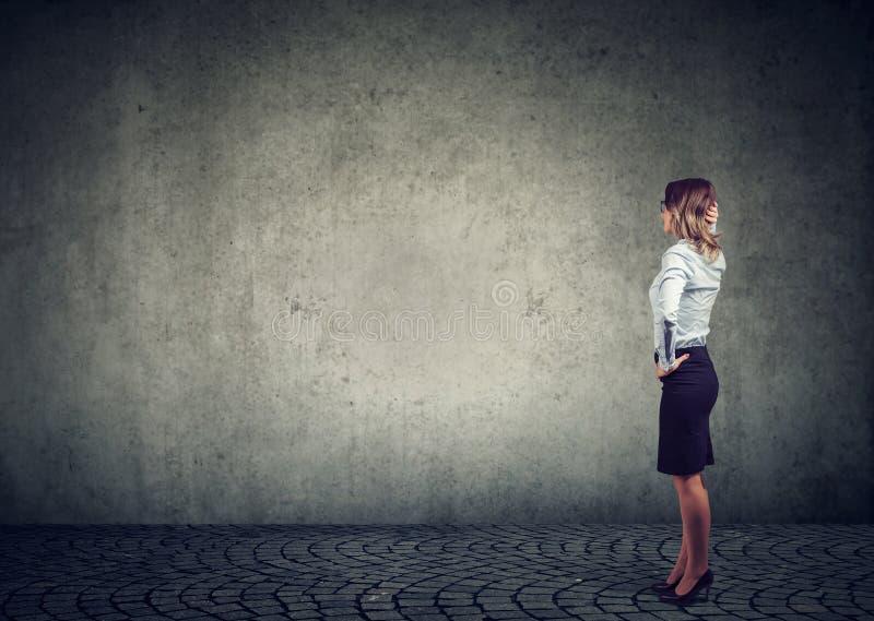 Ideia traseira da posição da mulher de negócio pela parede com mão na cabeça que quer saber que fazer em seguida o desafio Compri imagem de stock royalty free