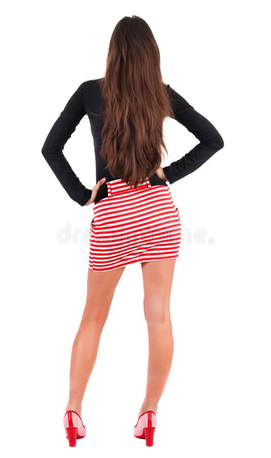 Ideia traseira de estar a mulher bonita nova no vestido vermelho. imagem de stock