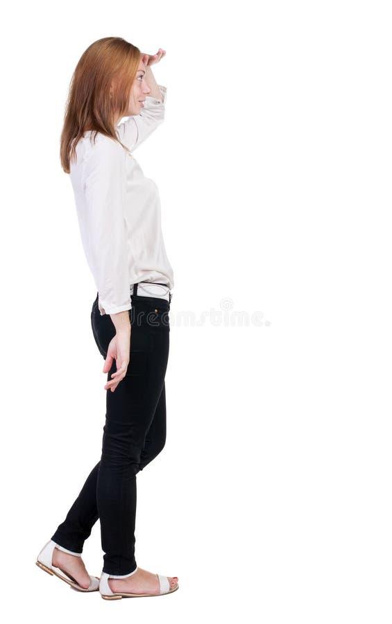 Ideia traseira de estar a mulher loura bonita nova nas calças de brim fotos de stock
