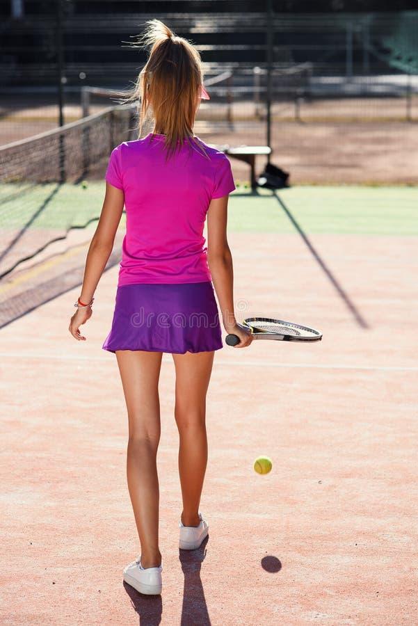 Ideia traseira de hitts fêmeas bonitos do jogador de tênis a bola de tênis à terra usando uma raquete ao andar no imagem de stock royalty free
