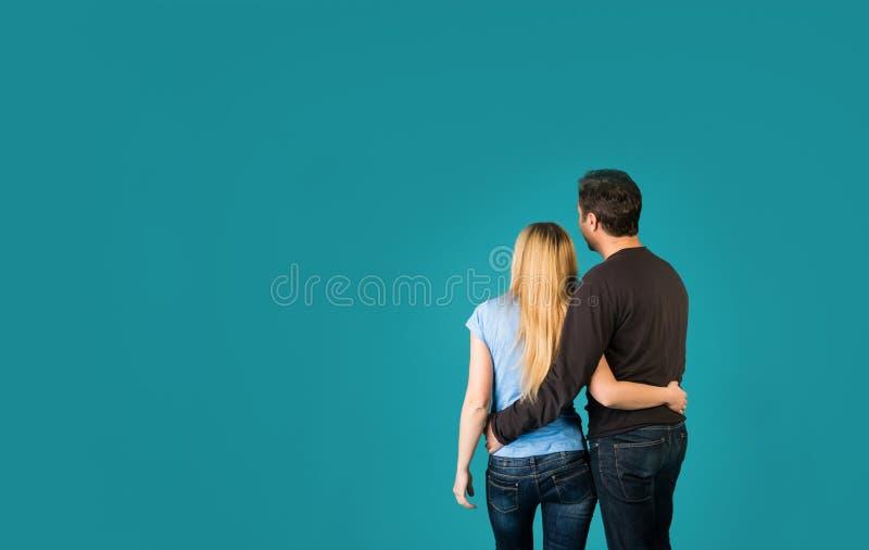 Ideia traseira de pares felizes do abraço com o Copyspace no fundo azul imagens de stock royalty free