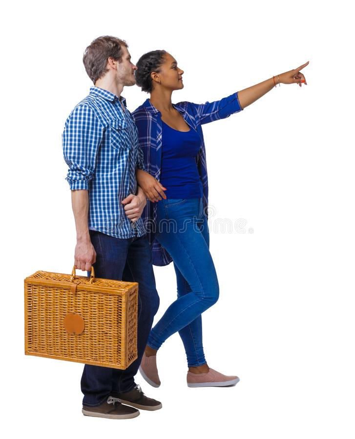 Ideia traseira de pares indo inter-raciais com um saco do piquenique que aponte em algum lugar fotos de stock