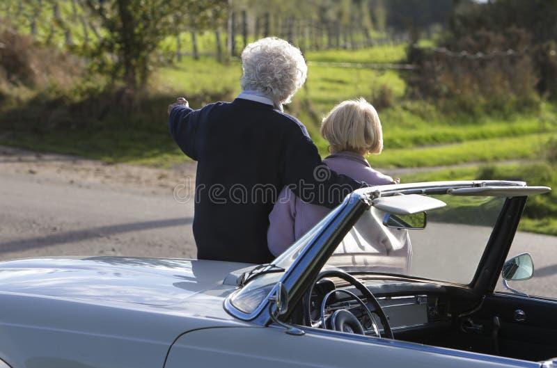Ideia traseira de pares maduros pelo carro no campo fotos de stock
