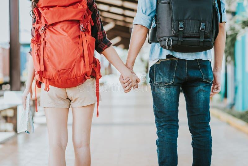 Ideia traseira de pares novos do viajante com a trouxa que guarda a mão no estação de caminhos-de-ferro foto de stock royalty free