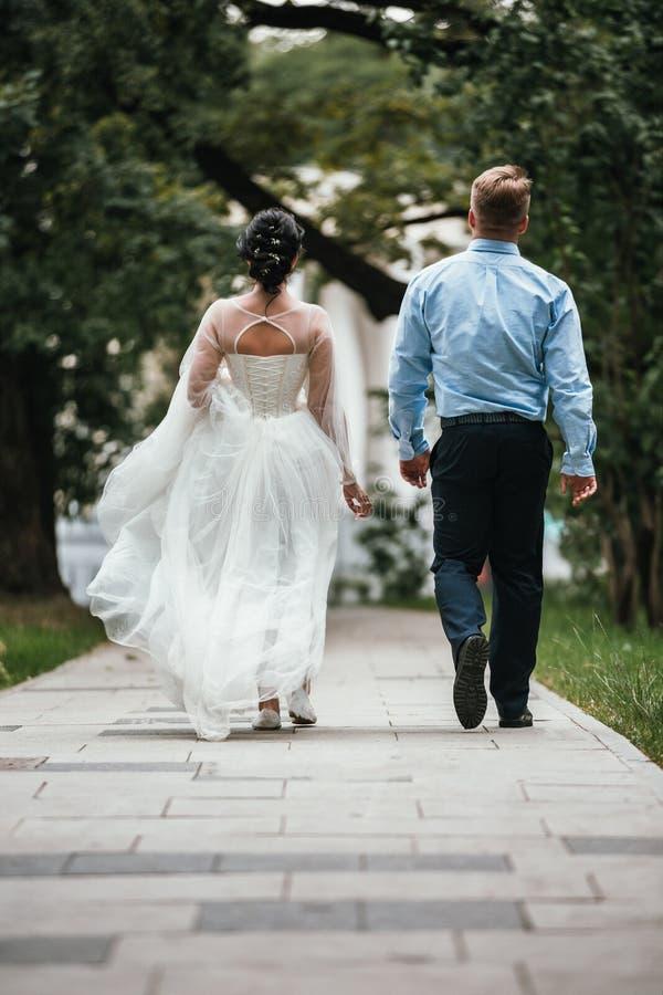 Ideia traseira de um par do recém-casado que abraça em um parque O par entra na distância fotos de stock