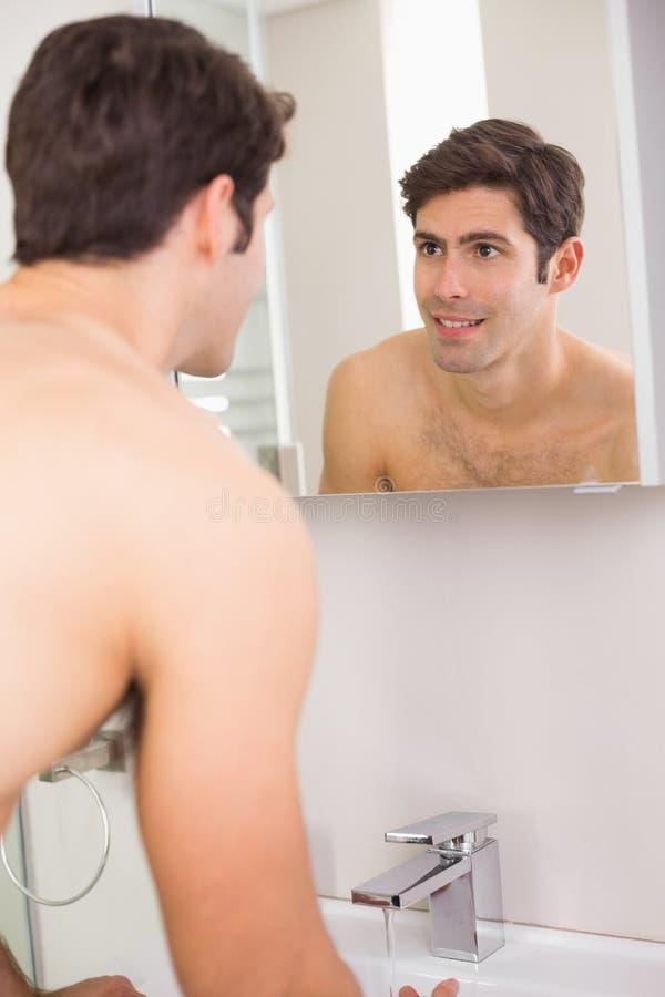 Ideia traseira de um sorriso novo no auto no espelho do banheiro imagens de stock