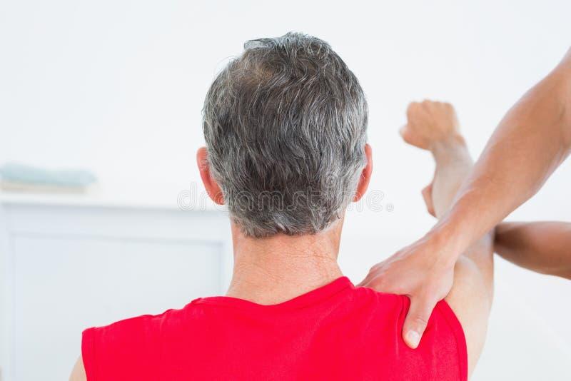 A ideia traseira de uma massagem do fisioterapeuta madura equipa o braço fotos de stock