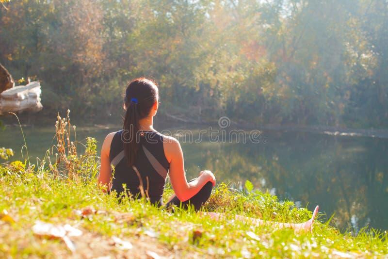 Ideia traseira do ner de assento da menina desportivo o lago do verão foto de stock royalty free