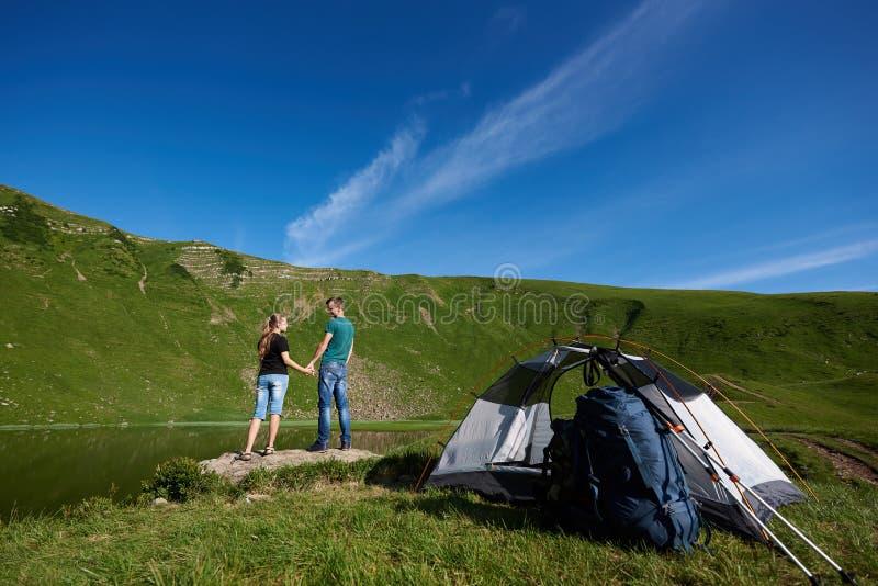 Ideia traseira do suporte bonito dos pares perto do acampamento contra a montanha verde poderosa fotografia de stock royalty free