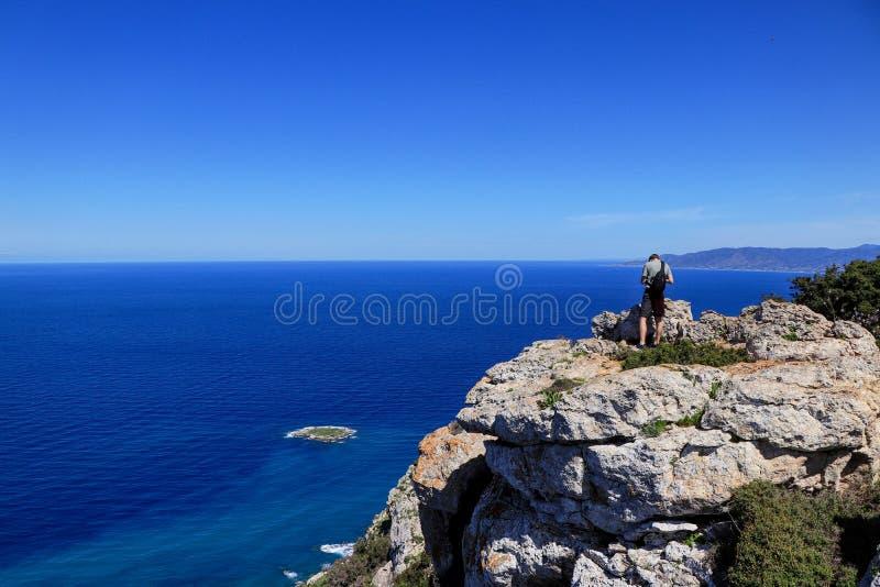 Ideia traseira do suporte do homem da liberdade no penhasco da rocha que olha o mar azul e a natureza cipriota Contraste entre o  imagens de stock