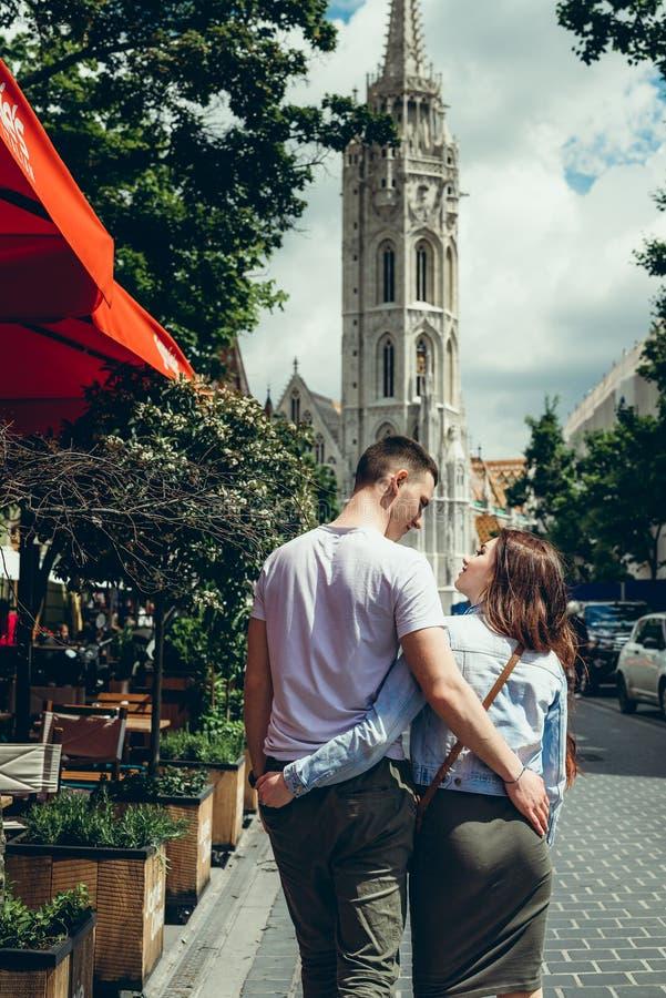 Ideia traseira dos pares novos felizes no amor que abraça ao andar ao longo da rua à catedral do ` s de St Matthew dentro imagens de stock royalty free