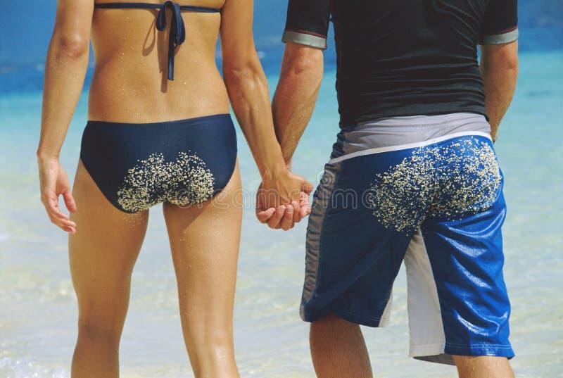 Ideia traseira dos pares novos que andam ao longo da praia imagens de stock royalty free