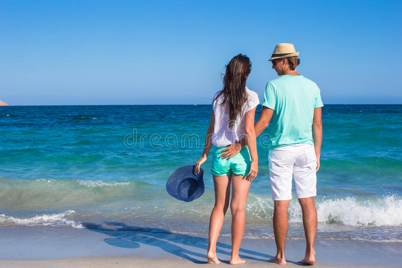 Ideia traseira dos pares novos que andam na praia durante foto de stock