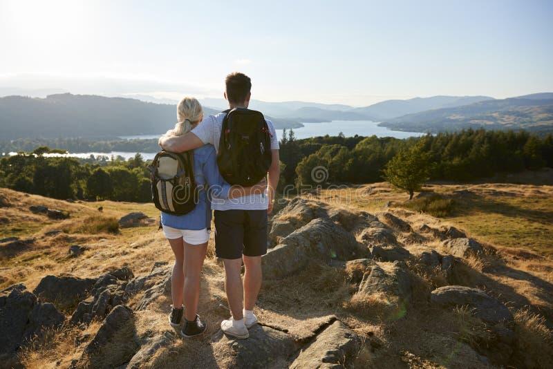 Ideia traseira dos pares que estão no auge do monte na caminhada através do campo no distrito Reino Unido do lago imagens de stock royalty free