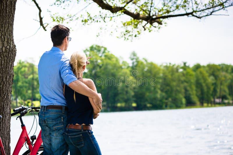 Ideia traseira dos pares que olham o lago fotografia de stock royalty free