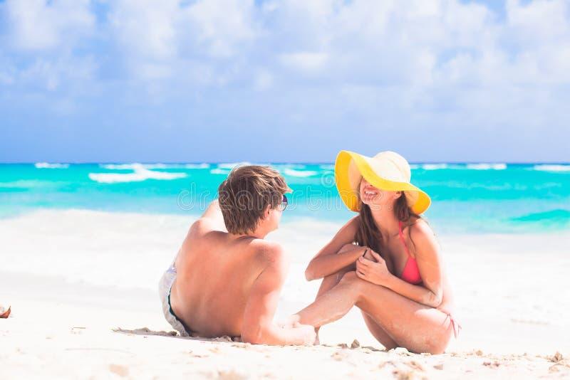 Ideia traseira dos pares que sentam-se na praia fotos de stock