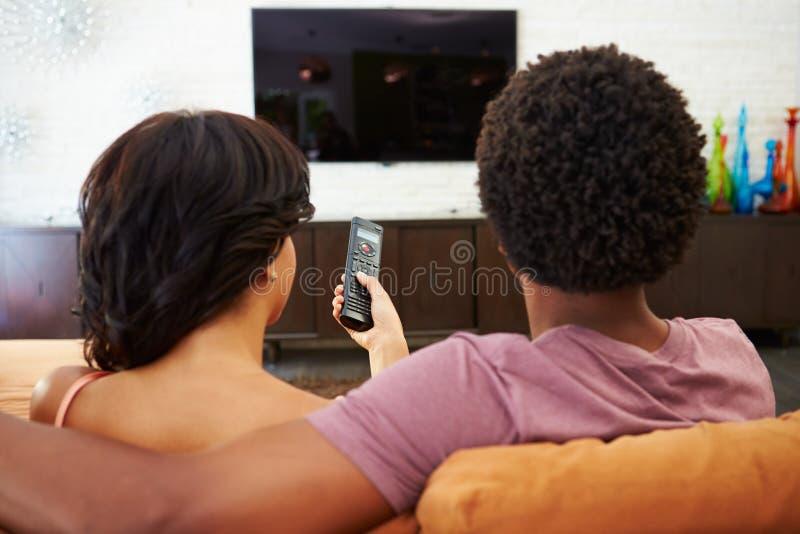 Ideia traseira dos pares que sentam-se na tevê de Sofa Watching junto fotografia de stock royalty free
