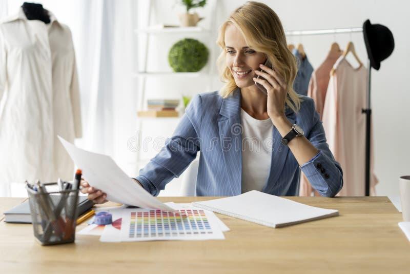 Ideias de giro na roupa Jovem mulher bonita que trabalha em esboços em seu estúdio perto da roupa que pendura no foto de stock