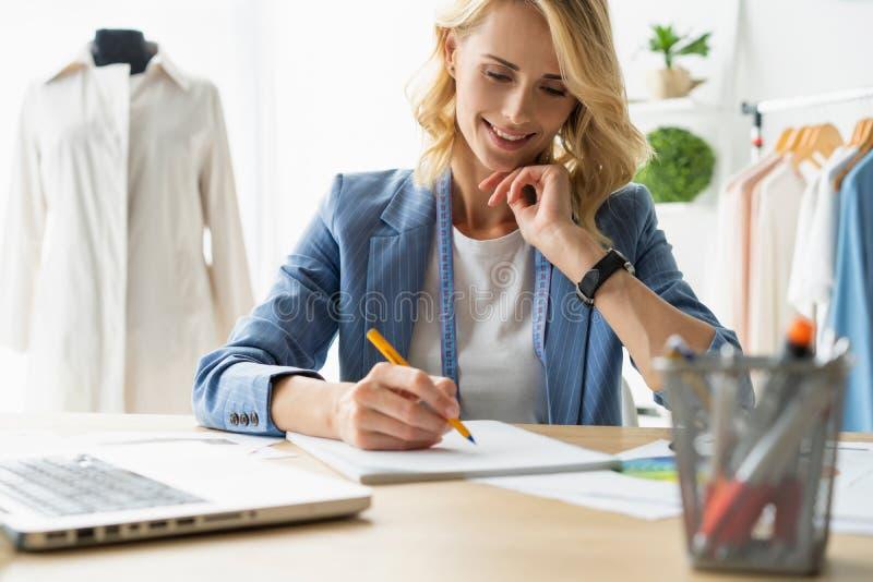Ideias de giro na roupa Jovem mulher bonita que trabalha em esboços em seu estúdio perto da roupa que pendura no imagens de stock royalty free