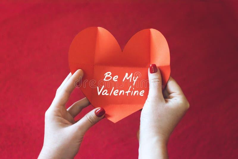 Ideias do cartão do dia de Valentim Cartão nas mãos das mulheres A mão fêmea com o cartão da forma do coração com seja meu Valent imagens de stock