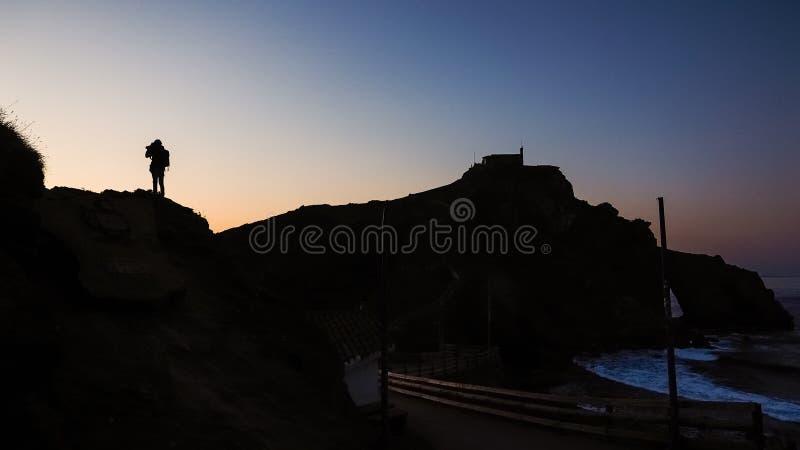 Ideias dos arredores de San Juan de Gaztelugatxe durante o por do sol, a silhueta do homem foto de stock