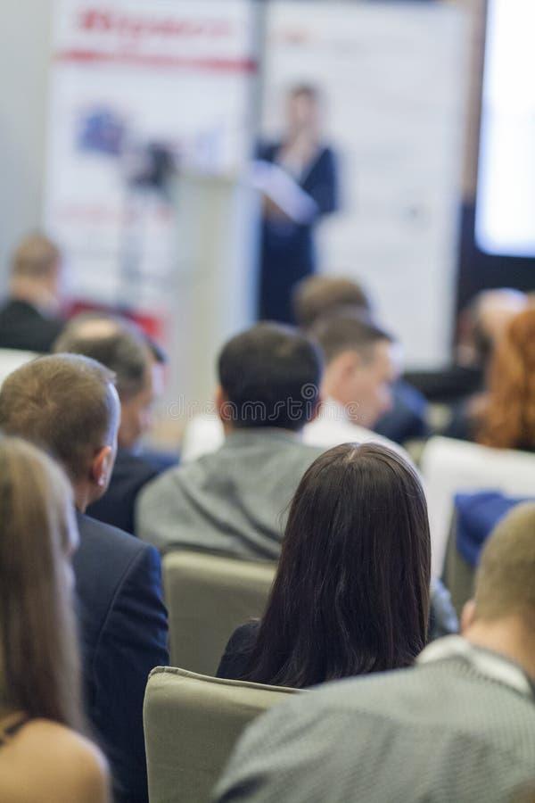 Ideias e conceitos do negócio Povos na conferência de negócio que escutam o anfitrião na frente da fase imagem de stock