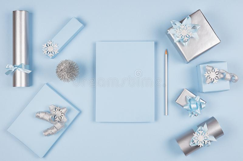Ideias para decorações do Natal do projeto e papel da prancha como o wishlist - caixas de presente metálicas azuis da luz suave e imagens de stock