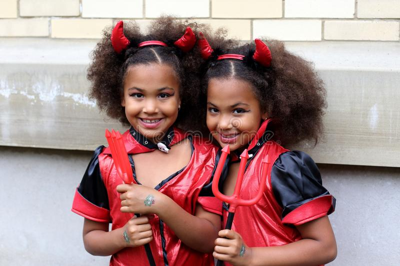 Identical African-American girl twins disguised as devils. To participate in the 2015 Just for Laugh`s twins parade, Montreal's Place-des-Arts sector royalty free stock photos