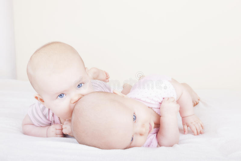 Identical baby twin sisters. Studio-shot of 6 month old identical baby twin sisters lying on bed royalty free stock photos