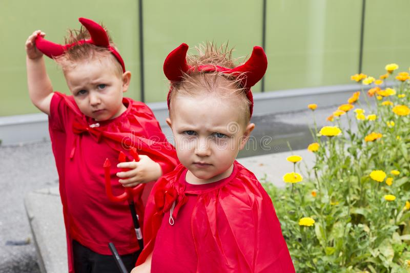 Identical toddler twin disguised as devil scowling with brother in soft focus background stock photos