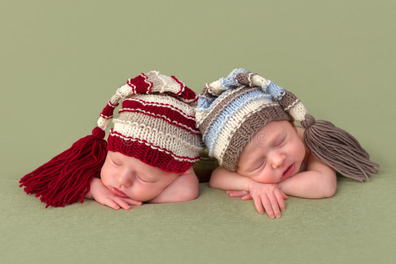 Identical twin babies with hats royalty free stock photography