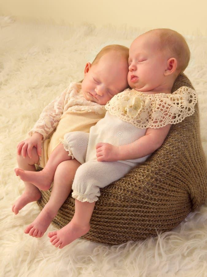 Identical twin babies. Three weeks old newborn identical twin babies dressed in lace stock photos