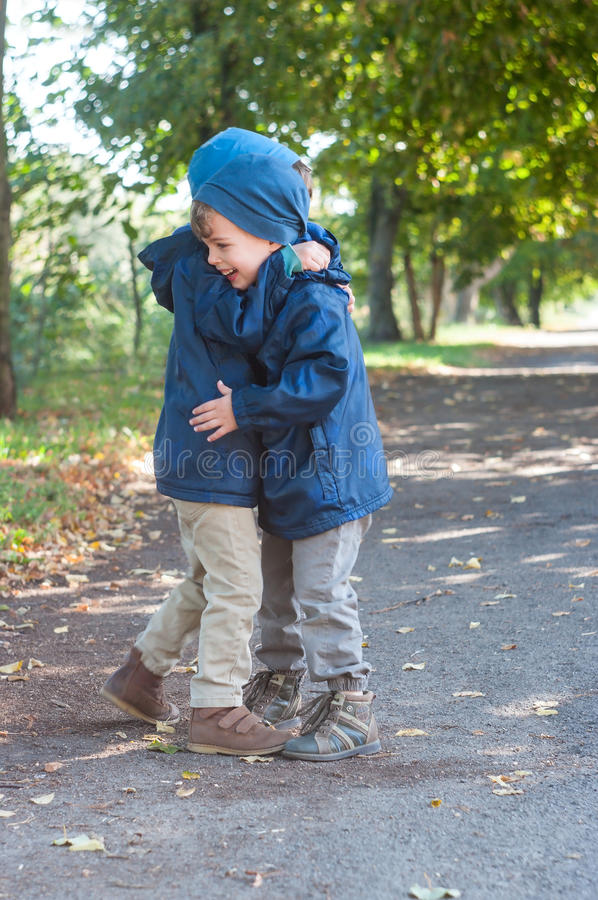 Identical twin brothers embrace each other royalty free stock photo