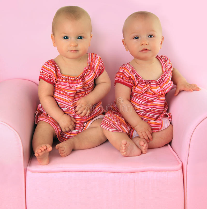 Identical twin girls. Identical twin baby girls, 10 months old stock photo
