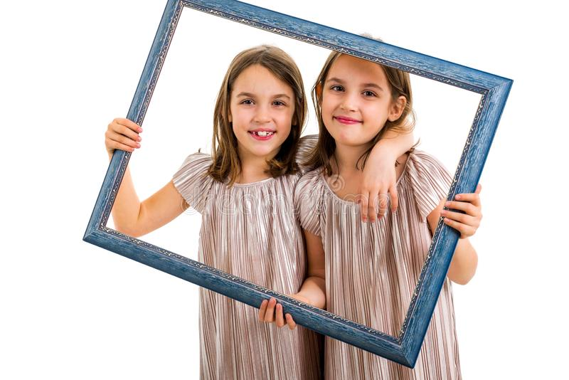 Identical twin girls are making happy expressions with picture frame. Children, sisters, girls posing in studio with picture frame, making different facial stock image