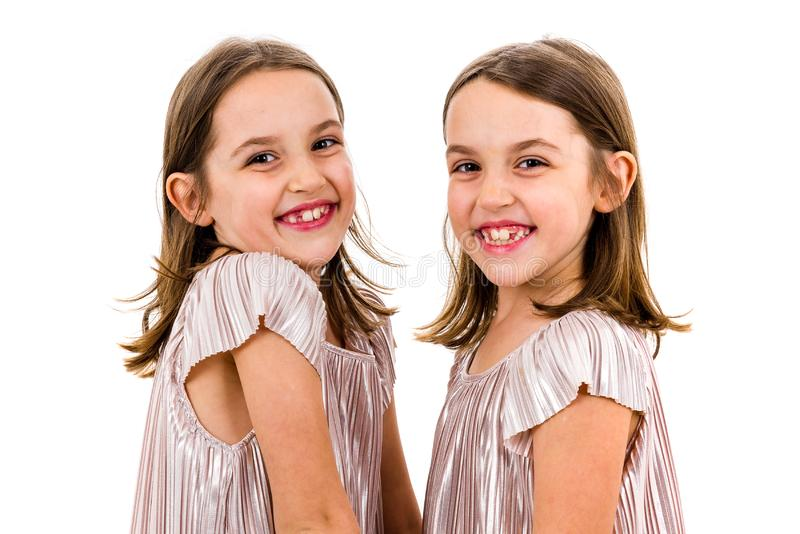 Identical twin girls sisters are posing for the camera. Happy twin sisters in dresses looking at the camera, laughing, smiling and holding hands. Profile view stock photo