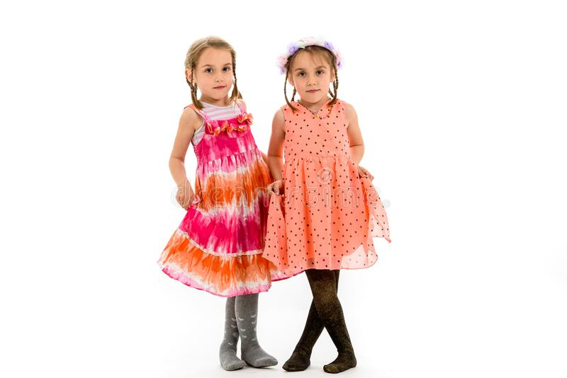 Identical twin girls sisters are posing for the camera. stock photos