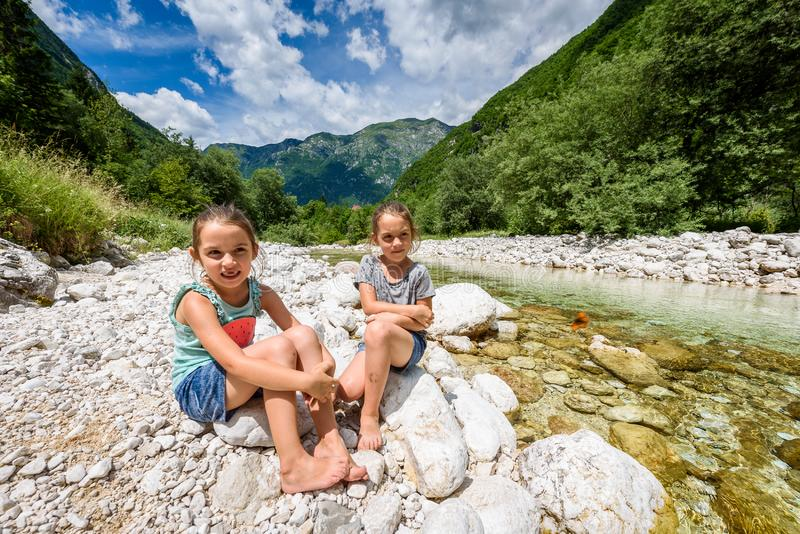 Identical twin girls sitting on river rock after nature hiking. Identical twin girls sitting on river bank after nature hiking. Children resting on rock in royalty free stock images