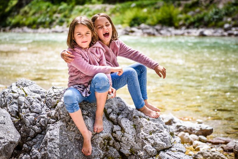 Identical twin girls sitting on river rock after nature hiking. Children resting on rock in mountain river enjoying sunny day. Active family life in nature royalty free stock photos