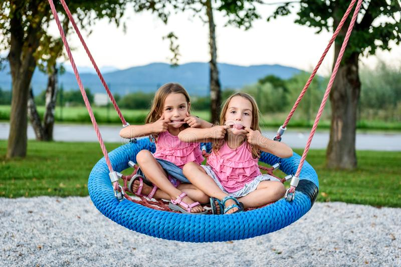 Identical twin girls on spider web nest swing on playground. Active Children playing with Giant Swing-N-Slide Monster Web Swing on outdoors playground in stock photos