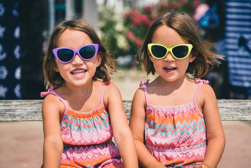 Identical twin girls on summer vacation posing for camera. Happy joyful children in the summertime with child sun glasses and pink dresses stock photography